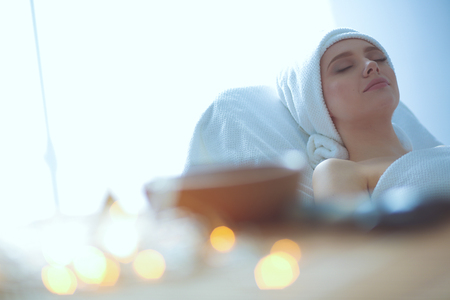 Young woman lying on a massage table,relaxing with eyes closed. Woman. Spa salon Stock Photo