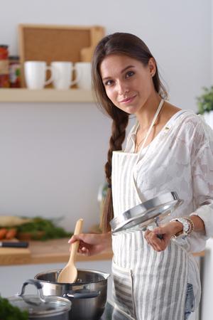 Kokende vrouw in keuken met houten lepel. Koken vrouw