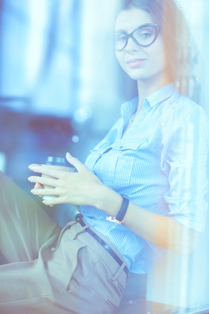 Young woman sitting at office table with laptop,view through window. Young woman