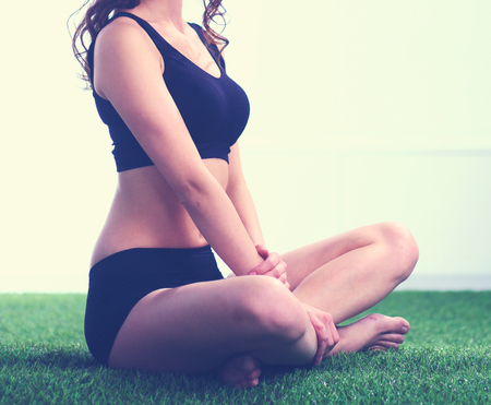Woman sitting with crossed legs on the green grass. Banco de Imagens