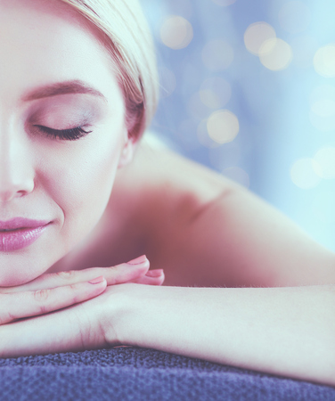 Young woman lying on a massage table,relaxing with eyes closed. Woman. Spa salon Banco de Imagens