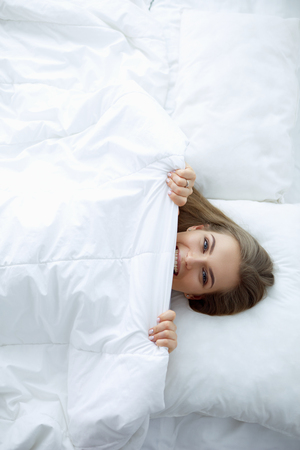 Face closeup of a beautiful young woman hiding her face under the sheet Stock Photo