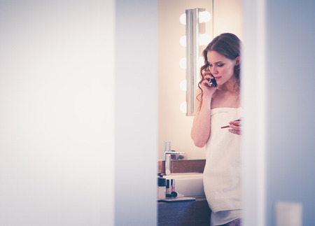 Young woman standing on bathroom with phone. Stock Photo
