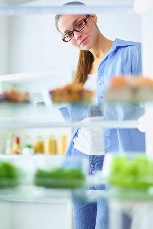 Portrait of female standing near open fridge full of healthy food, vegetables and fruits. Standard-Bild - 111602438