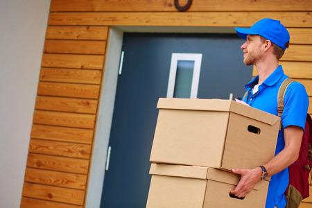 Smiling delivery man in blue uniform delivering parcel box to recipient - courier service concept.