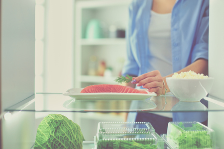 Portrait of female standing near open fridge full of healthy food, vegetables and fruits. Фото со стока - 111683689
