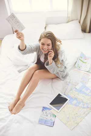 Relaxed young woman sitting on bed with a cup of coffee and digital tablet
