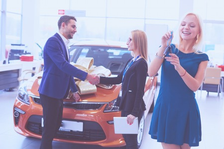 Woman receiving car keys from a dealer