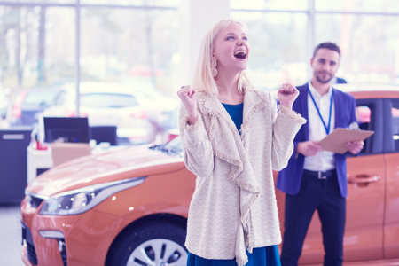 Dealer with woman stands near a new car in the showroom Stock Photo