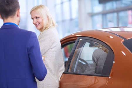 Dealer with woman stands near a new car in the showroom Stockfoto