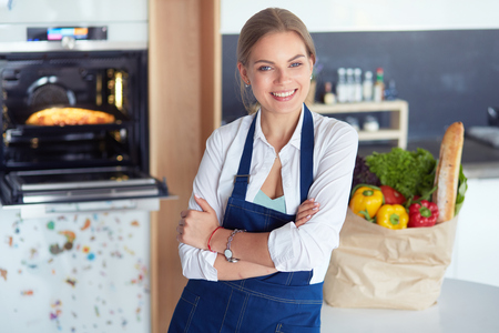 Portrait of young woman standing with arms crossed against kitchen background Фото со стока - 113892116
