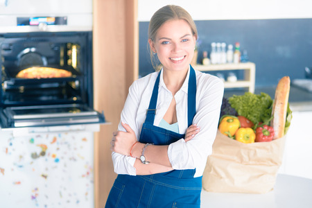Portrait of young woman standing with arms crossed against kitchen background Фото со стока - 113604665