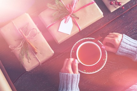 Woman sitting on the desk with christmas gift box. Hands of woman Archivio Fotografico