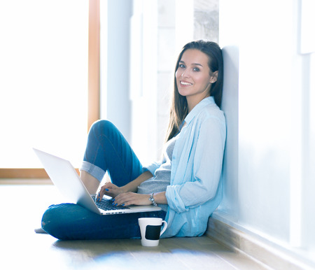 Young beautiful woman at home sitting on the floor with laptop. Young beautiful woman. Standard-Bild