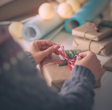 Hands of woman decorating christmas gift box. Hands of woman. Christmas.