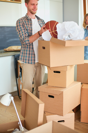 Couple unpacking cardboard boxes in their new home. Reklamní fotografie