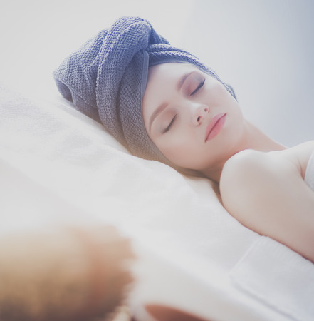 Young woman lying on a massage table,relaxing with eyes closed. Woman. Spa salon Imagens