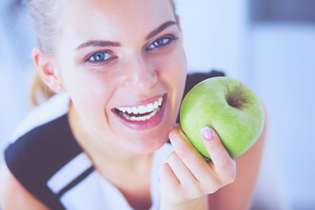 Close up portrait of healthy smiling woman with green apple.