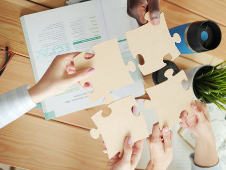 Close-up photo of businesspeople holding jigsaw puzzle.