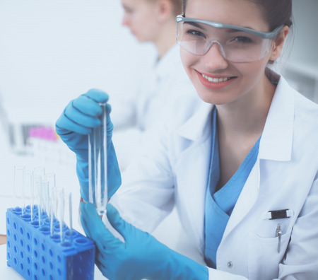 Woman researcher is surrounded by medical vials and flasks Stock Photo
