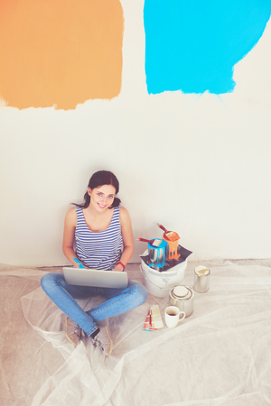 Young woman portrait while painting new apartment, sitting with laptop. Banque d'images - 119697707