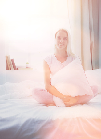 Cute woman holding a pillow while sitting on her bed