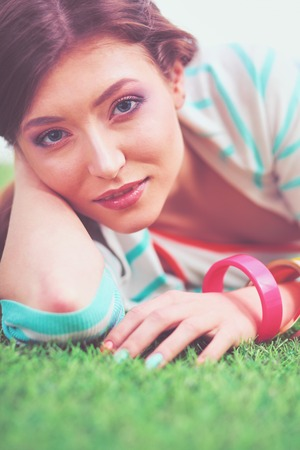 Beautiful young woman lying on the green grass Stock Photo