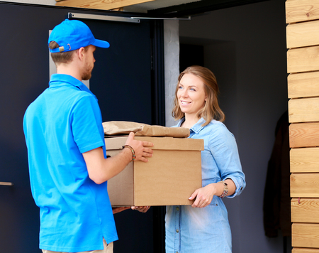 Smiling delivery man in blue uniform delivering parcel box to recipient - courier service concept.