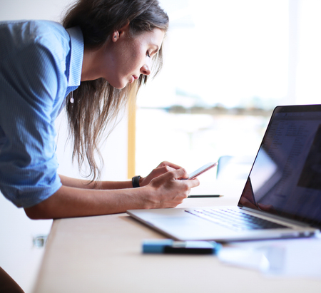 Young woman sitting at office table with laptop Imagens - 120071472