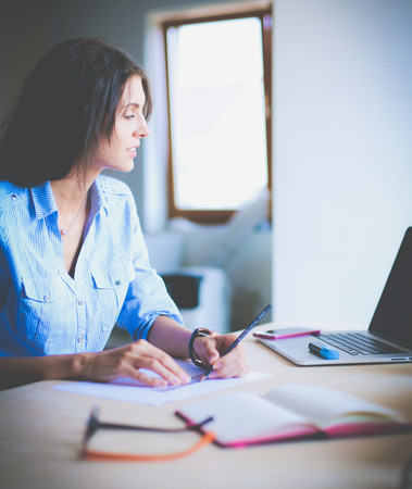 Young woman sitting at office table with laptop.
