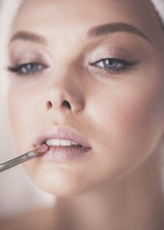Una foto de una mujer joven que aplica polvos faciales en el baño.