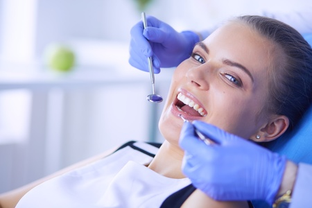 Young Female patient with open mouth examining dental inspection at dentist office. Stock Photo