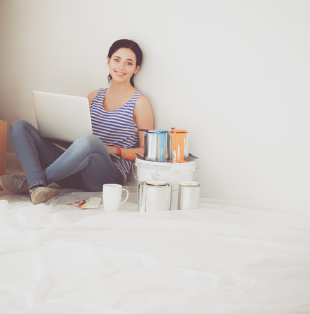 Young woman portrait while painting new apartment ,sitting with laptop. Imagens