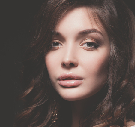 Ritratto del volto di donna giovane e bella. Isolato su sfondo scuro.