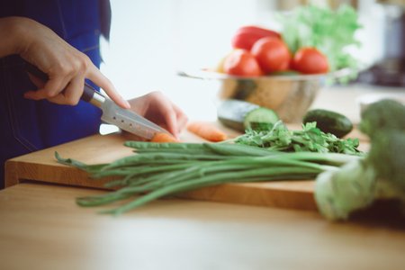 Young woman cutting vegetables in kitchen at home Imagens