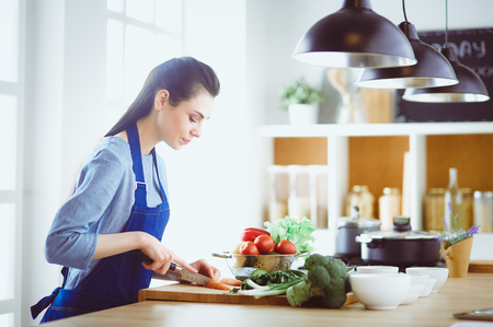 Young woman cutting vegetables in kitchen at home Stock fotó