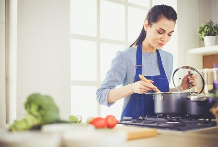 Mujer de cocina en cocina con cuchara de madera