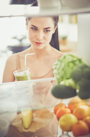 Smiling woman taking a fresh vegetable out of the fridge, healthy food concept