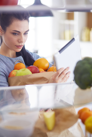 Smiling woman taking a fresh fruit out of the fridge, healthy food concept