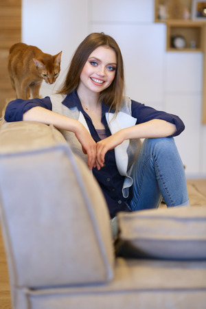 Woman sitting on her white sofa in white pullover Banco de Imagens
