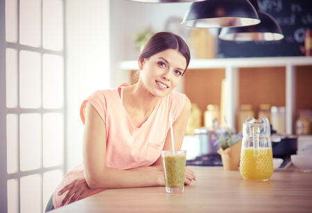 Beautiful young woman using a digital tablet in the kitchen. Imagens