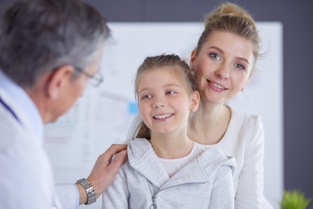 Little girl with her mother at a doctor on consultation Imagens