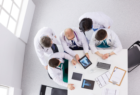 Medical team sitting and discussing at table, top view