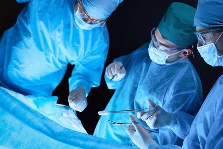 Groupe de chirurgiens au travail en salle d'opération aux tons bleus. Équipe médicale effectuant l'opération