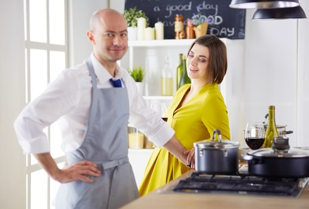 Attractive couple in love cooking and opens the wine in the kitchen while they cook dinner for a romantic evening 版權商用圖片