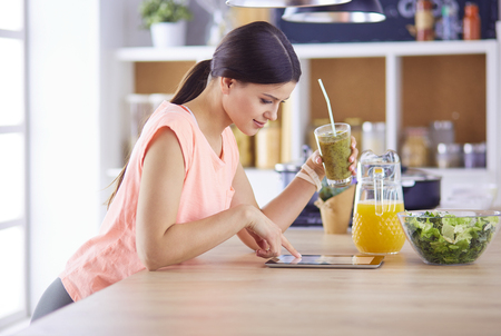 Beautiful young woman using a digital tablet in the kitchen