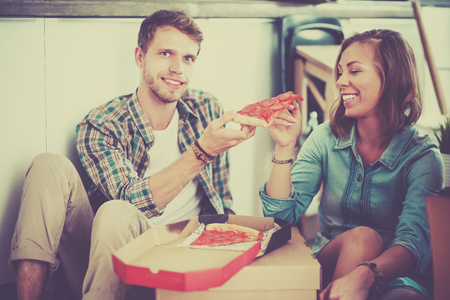 Young couple have a pizza lunch break on the floor after moving into a new home with boxes around them 版權商用圖片