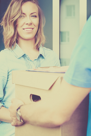 Smiling delivery man in blue uniform delivering parcel box to recipient - courier service concept Stock Photo