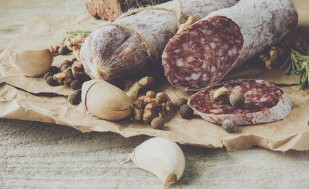 Italian salami wih sea salt, rosemary, garlic and nuts on paper. Rustic style. Close up.