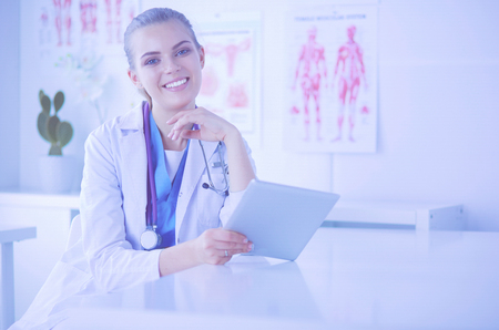Young attractive female doctor looking at x-ray image Imagens